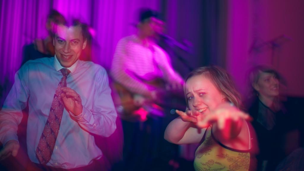 Koordinaattori ja vapaaehtoisia tanssimassa, sekä bändi taustalla soittamassa