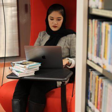 Nuori nainen istuu kirjastossa läppäri sylissä.