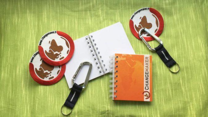 Changemaker-tuotteet: kangasmerkki, avainlenkki ja muistikirja