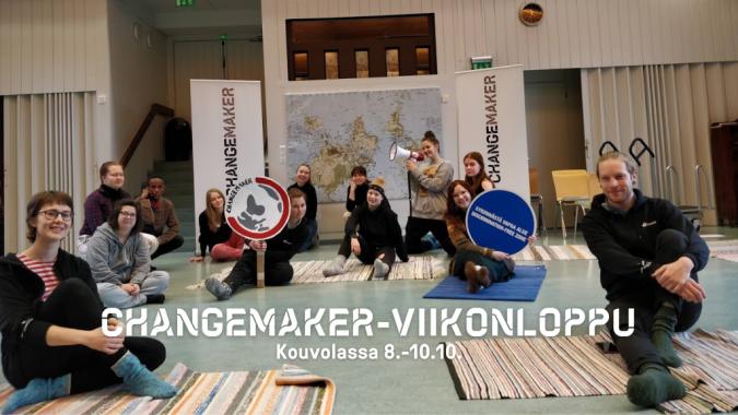 Changemaker-viikonlopun osallistujia, joilla on Changemkaer-kylttejä. Lattialla on räsymattoja ja einällä maailman kartta.
