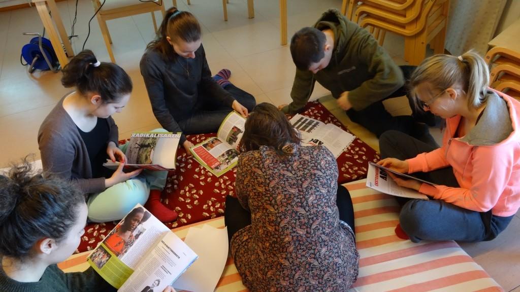 Osallistujia tutkimassa Globalistin Radikalisaatiosta kertovia juttuja.