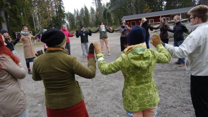 Osallistujia ulkona leikkimässä taputusleikkiä.