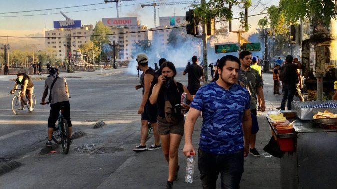 Mielenosoittajat suojaavat kasvonsa poliisisotilaiden protestien hajottamiseen käyttämää kyynelkaasua vastaan Chilen pääkaupungissa Santiagossa. Taustalla Plaza Italia, josta muodostui viime vuoden mielenosoitusten keskipiste.
