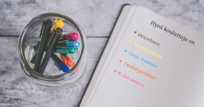 Kouluttajakoulutuksen kansikuva. Kuvassa kyniä sekä vihko, jossa lukee hyvän kouluttajan ominaisuuksia, joita ovat innostavuus, asiantuntevuus ja rohkeus.