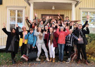Changemaker-viikonlopun osallistujat seisovat leirikeskuksen edessä ja heiluttavat kameralle