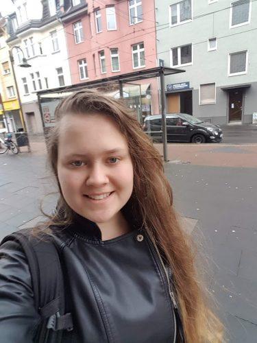 Joanna ottaa itsestään kuvaa ja hymyilee. Hänellä on pitkät ruskeat hiukset. Taustalla näkyy värikkäirä rakennuksia.