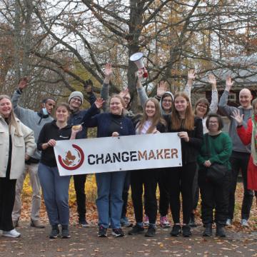 Changemaker-viikonlopun osallistujia Changemaker-kyltin kanssa