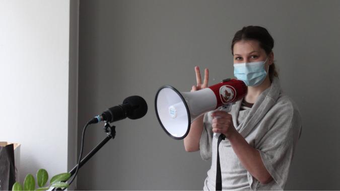 Iida Silfverhuth näyttää mikrofonin edessä voiton merkkiä. Kädessään hänellä on megafoni.