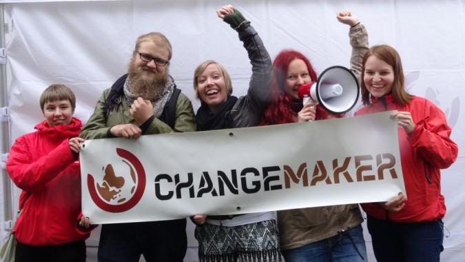 Vapaaehtoisia Changemaker-bannerin kanssa