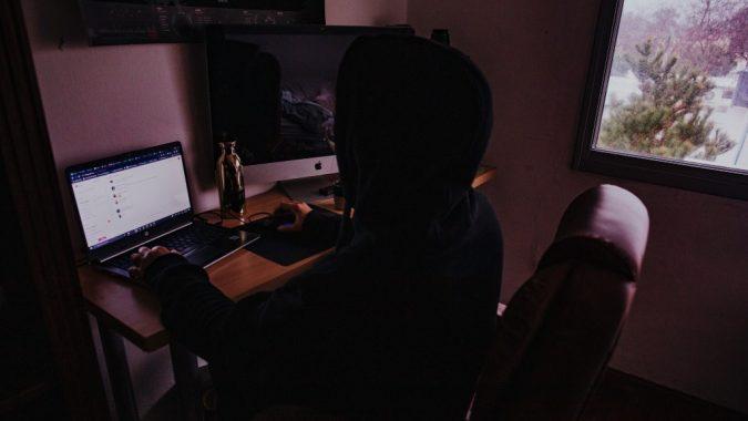 Henkilö istuu tietokoneen äärellä pimeässä huoneessa.
