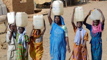 Naisia kantamassa vettä