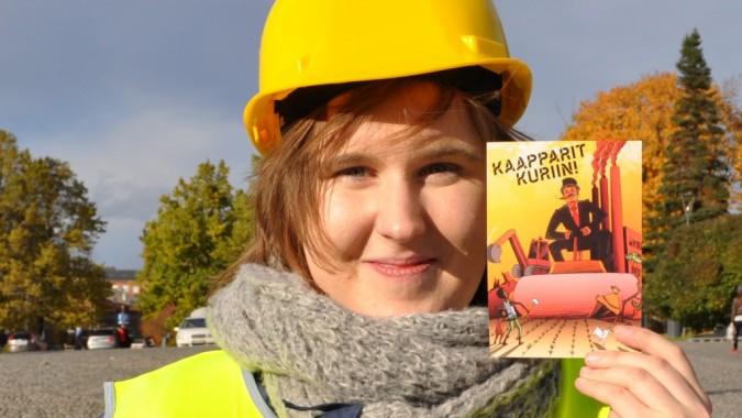 Changemakerin puheenjohtaja Elina Tyynelä piitelee kädessään Kaapparit kuriin! -kampanjan flaieria.