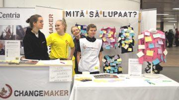 Changemakerin ständi, minä lupaan -kyltti ja vapaaehtoisia.