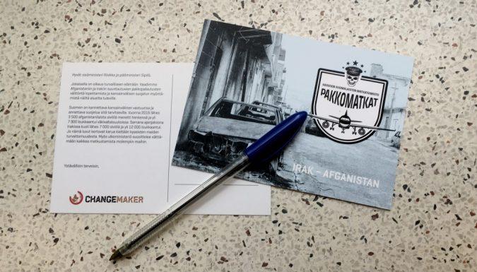 Pakkomatkat-kampanjan vetoomuspostikortti ja kynä
