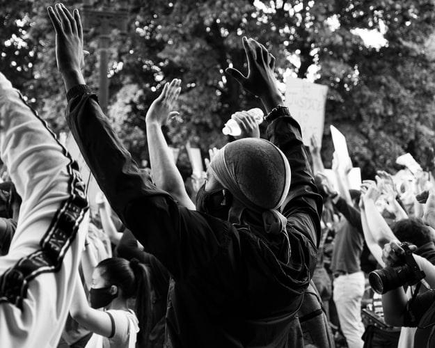 Mustavalkoisessa kuvassa mies, jolla on kasvomaski, on nostanut kätensä ilmaan