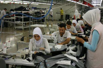 Työntekijöitä ompelemassa vaatetehtaalla