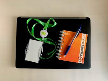 tietokone, kulkulupa, avainnauha ja muistikirja