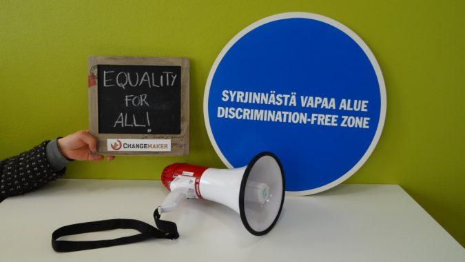 Syrjinnästä vapaa alue -merkki ja equality for all teksti, sekä megafoni
